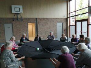 senioren zitten in een kring en spelen met een bal